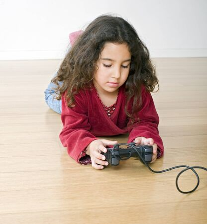 little girl playing playstation lying on the floor photo