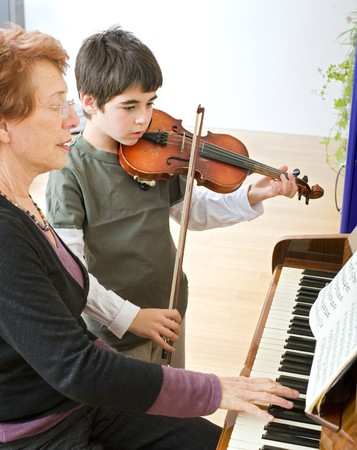 child playing the violin with his teacher on the piano