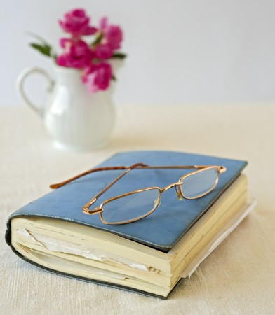 writing on glass: closed notebook and old glasses