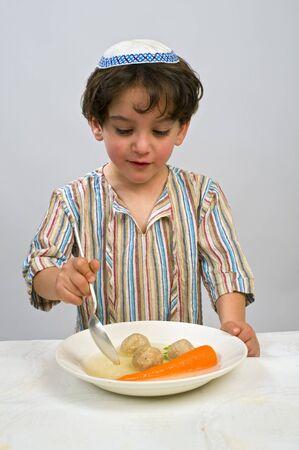 Jwish young boy having matzo ball soup Stock Photo - 4339973