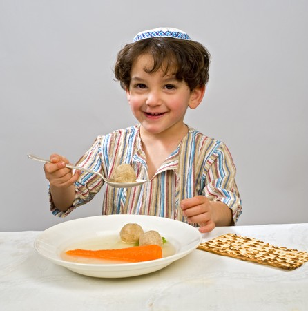 Jwish young boy having matzo ball soup Standard-Bild