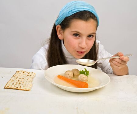 matzo: Jwish girl eating a matzo ball soup in passover