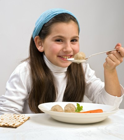 matzoh: Jwish girl eating a matzo ball soup in passover