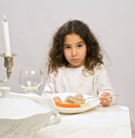 Jwish girl eating a matzo ball soup in passover photo