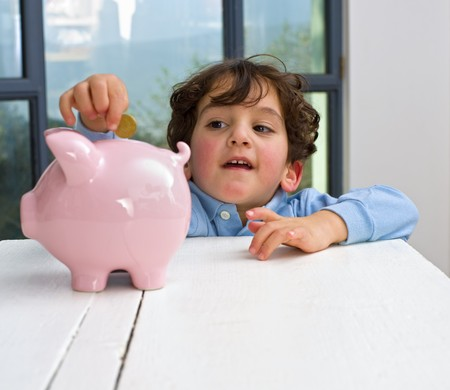 young boy holding a piggy bank Stock Photo