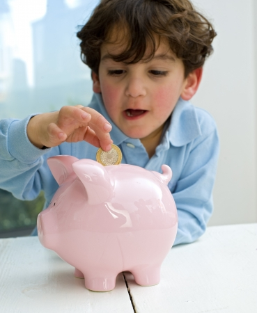 young boy inserting a coin in a piggy bank