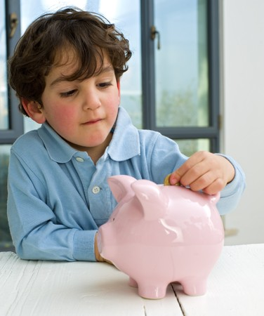 inserting: young boy inserting a coin in a piggy bank