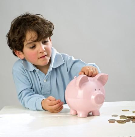 Junge Sie eine Münze in einem Sparschwein Standard-Bild - 4346916