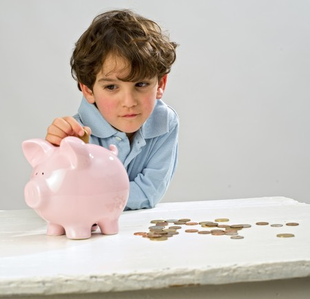 boy inserting a coin in a piggy bank
