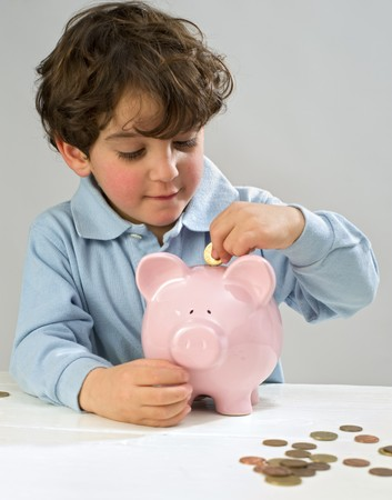 boy inserting a coin to a piggy bank