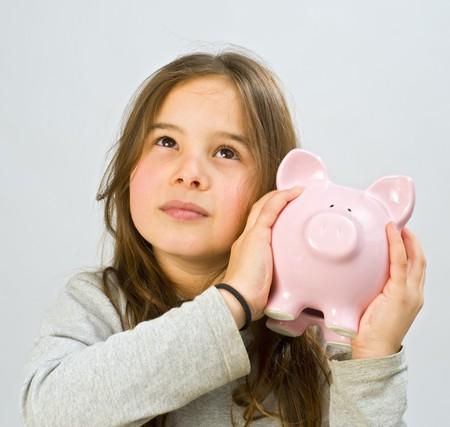 girl shaking a piggy bank Stock Photo