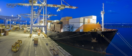 loading dock: cargo ship at dock by night panorama Stock Photo