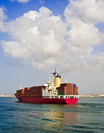 fully loaded cargo ship leaving the port