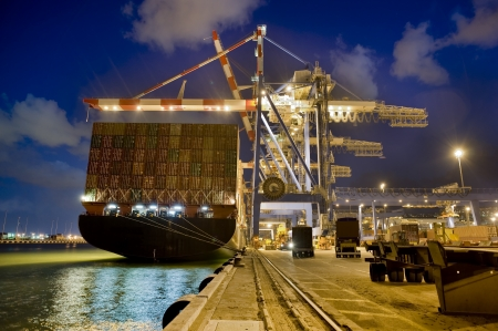 loading cargo: cargo ship at dock by night from behind