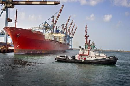 Schlepper ziehen einem Frachtschiff aus dem Dock Standard-Bild - 4548173