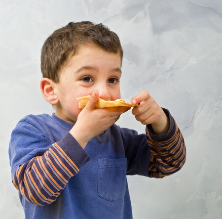young boy eating homemade pizza