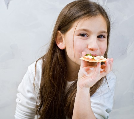 young girl eating homemade pizza