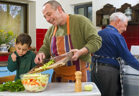 father child and grandfather cooking in the kitchen together Stock Photo
