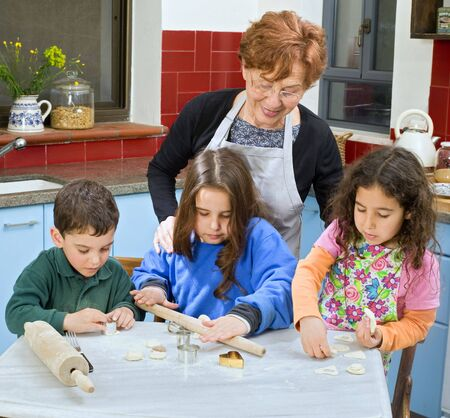 grandmother and grandchilds baking cookies together photo
