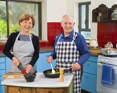 thier: senior couple cooking at thier kitchen at home