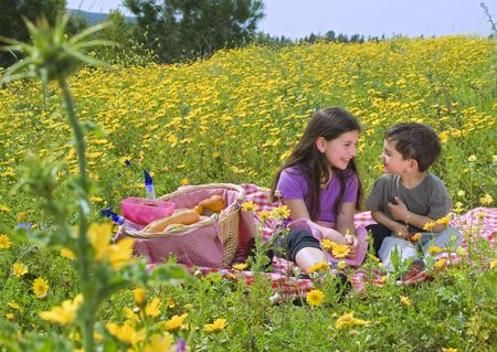 little boy and girl having a picnic in a yellow flowers field photo