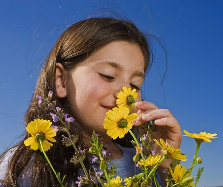 young girl smelling yellow wild flowers photo