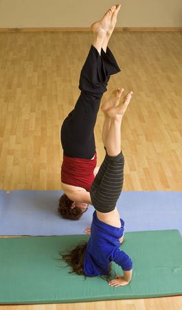 gymnastics sports: grandmother and child exercising doing a headstand together