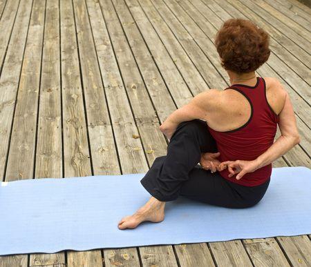 senior woman doing yoga on a deack floor