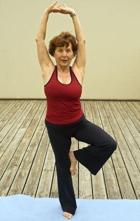 senior woman doing yoga on a deck floor Standard-Bild