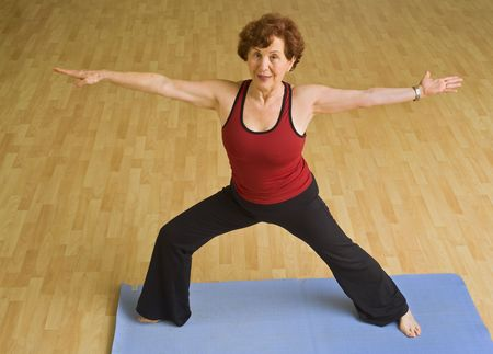 senior woman doing yoga in a gym photo