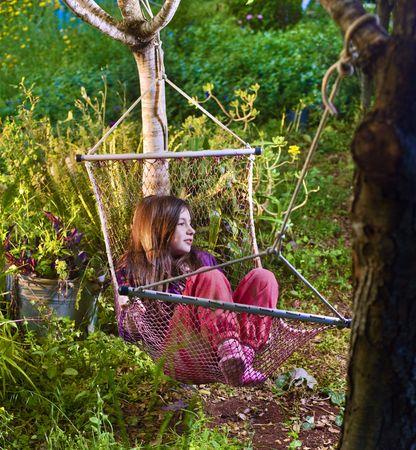 little girl lying in a hammock in backyard