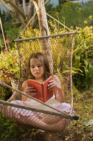 young girl reading a book on a hammock photo