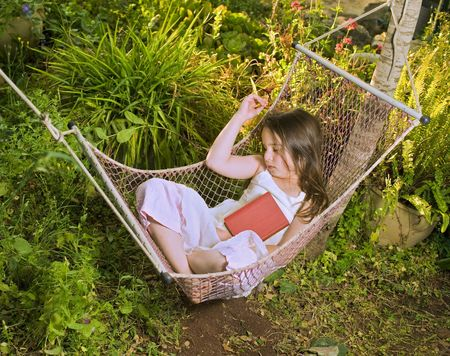 little girl sleeping in a hammock with a book photo