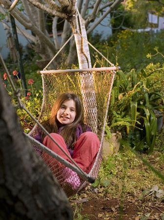 little girl lying in a hammock in backyard photo