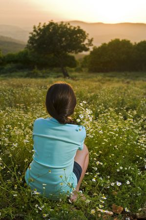girl holding bouqet of white flowers in a field at sunset Stock Photo - 4865689