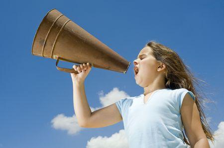Mädchen schreiend mit einem Megaphon gegen blauen Himmel Standard-Bild - 5214165
