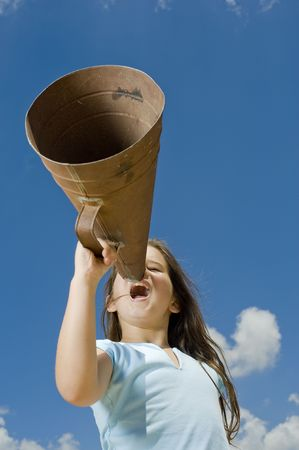 girl shouting with a megaphone against blue sky
