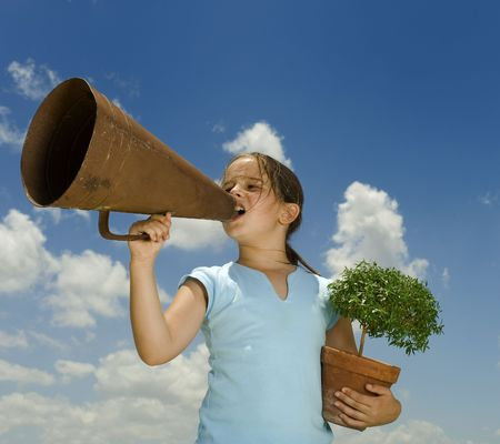 young girl holding and small tree and shouting with a megaphone against blue sky Stock Photo