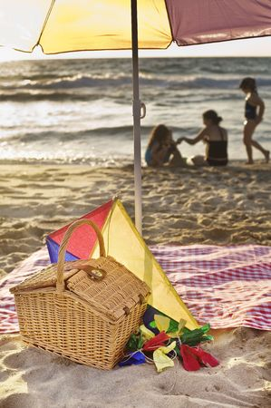 picnic blanket: picnic basket, kite, blanket, parasol and family in backgroud at he beach.