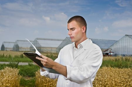 plant science: Agriculture scientist making notes in the field with greenhouses in background Stock Photo