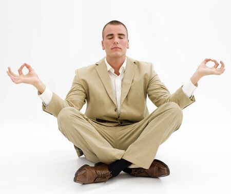 businessman meditating in lotus position over white Stock Photo - 5486454