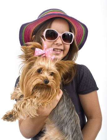 Young girl with sunglasses and hat, holding a yorkshire terrier dog photo