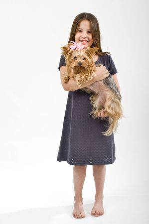 Young girl holding a yorkshire terrier dog on white photo