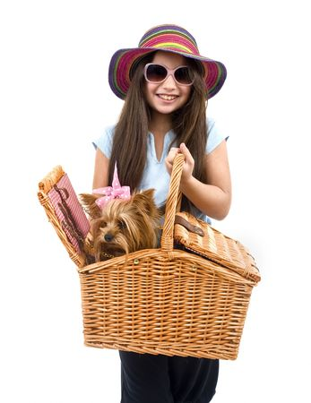 girl wearing a strow hat and pink sunglasses, holding a picnic basket with yorkshire terrier dog photo