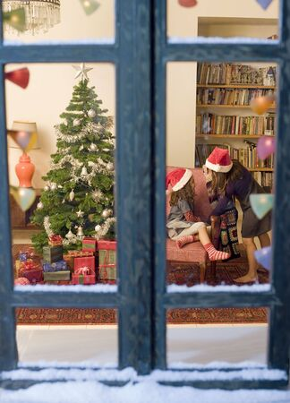 two little girls opening chrismas presents watched from a snowy window