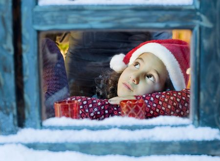 Little girl with a Santa hat  looking outside