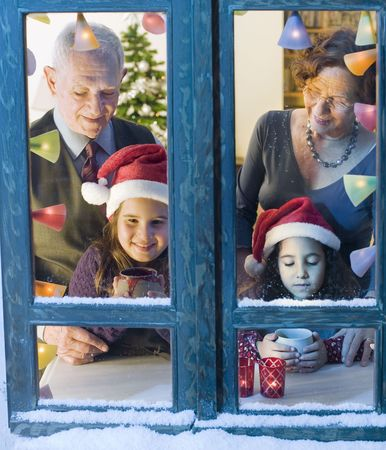 Grandparents and granddaughter at the window on Christmas eve. Stock Photo