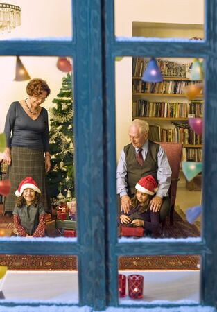 grandparents giving Christmas present to their little granddaughters photo