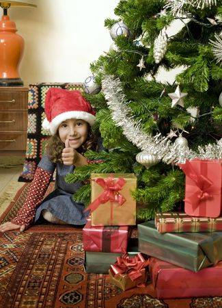 thumps up: little girl with thumps up  behind Christmas tree