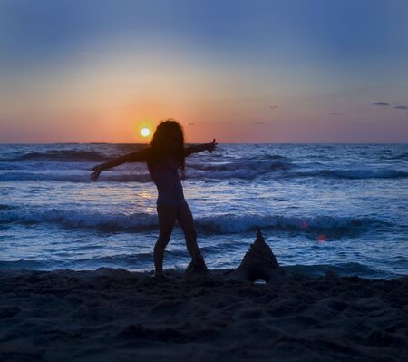 little girl's silhouette on the beach at sunset Stock Photo - 5614744